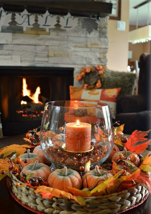 a basket with faux pumpkins and berries and a glass with a candle and pebbles for the fall