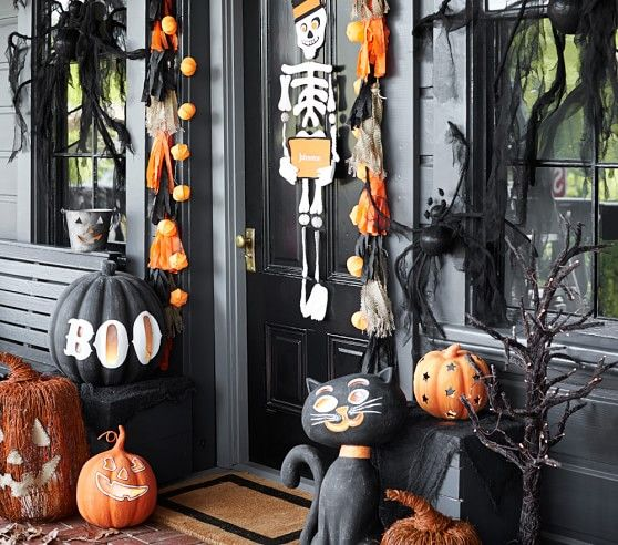 a front door decorated with a skeleton for Halloween