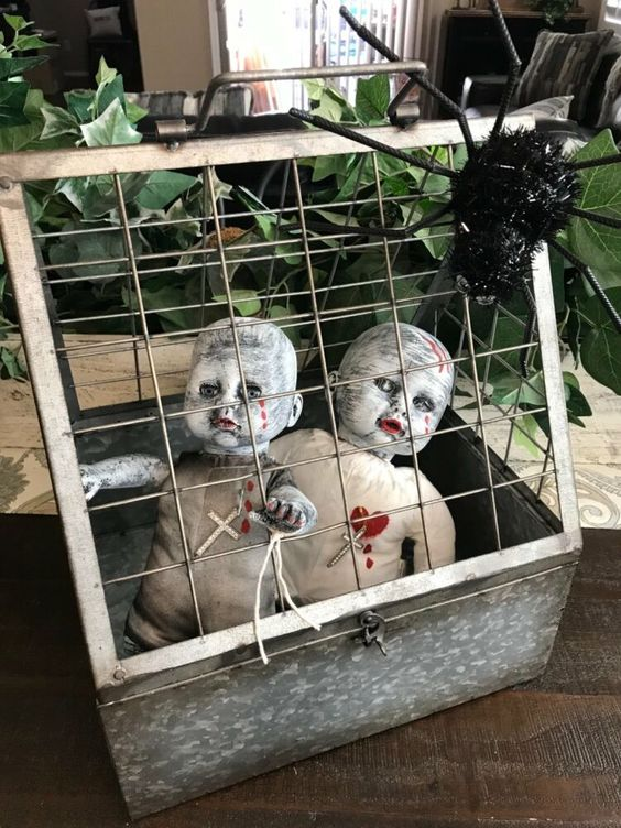 a cage with scary babies and a giant spider is a bold and spooky decoration you can make for Halloween