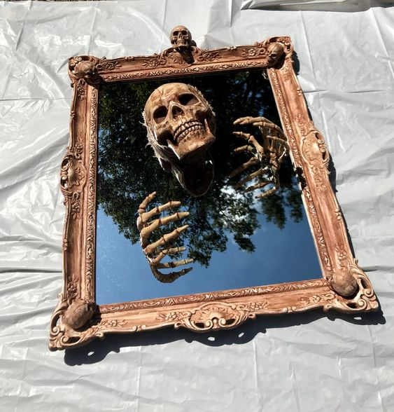 a chic and refined Halloween decoration of a mirror, a skull and skeleton hands can be DIYed for your space
