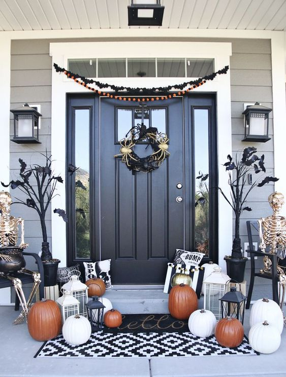 a chic classic Halloween porch with black trees with bats, a spider wreath, white, orange and gold pumpkins and lanterns