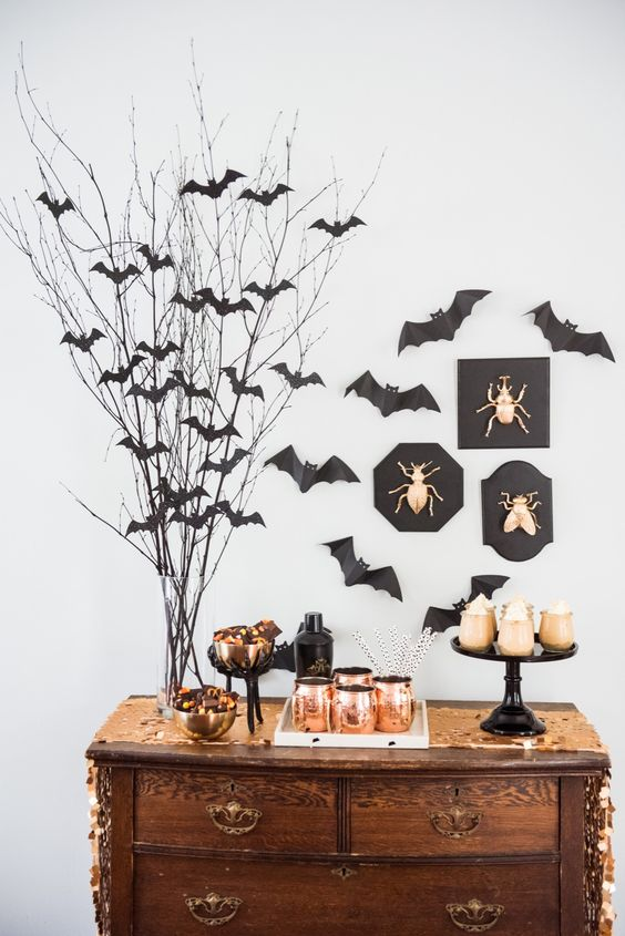 a chic dessert table with lots of bats around, gold bugs on the wall and copper mugs is ideal for Halloween