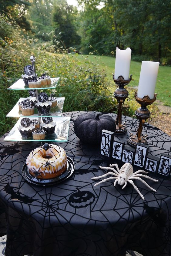 a classic Halloween dessert table with a whimsy black tablecloth, spiders, a black pumpkin and pillar candles