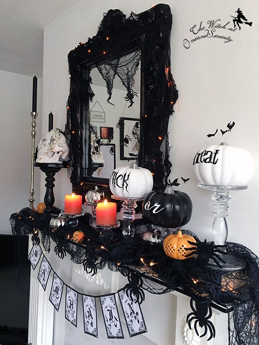 a classic Halloween mantel with lights, black and orange candles, black and white pumpkins, a printed bunting and spiders