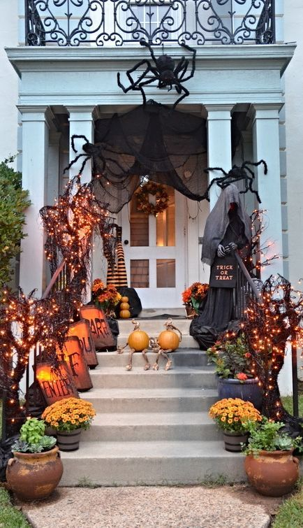 a classic Halloween porch with a ghost, lights on mini trees, potted blooms, black fabric and giant spiders plus pumpkins