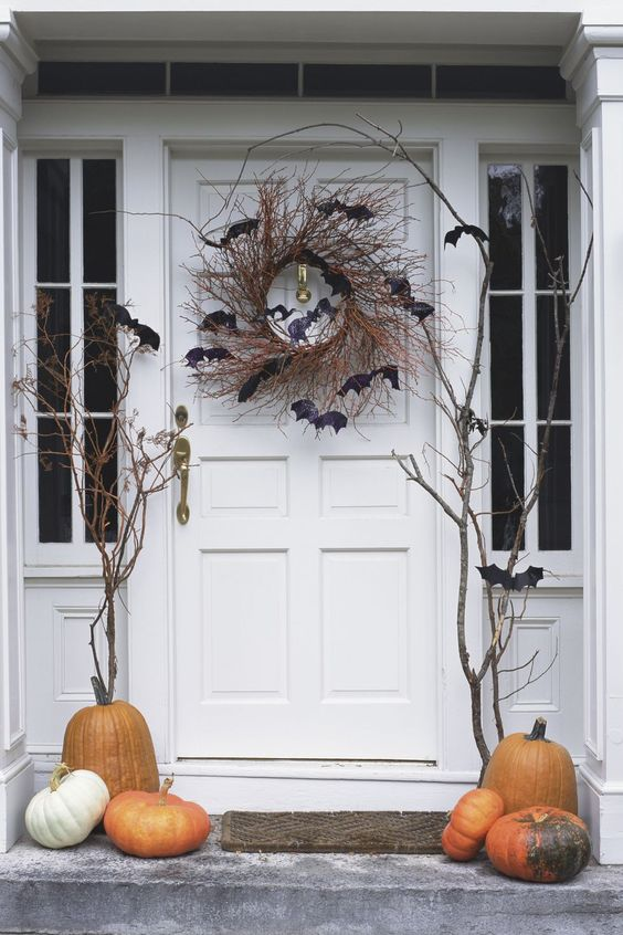 a classic Halloween porch with pumpkins and a vine wreath with bats and branches is spooky and cool