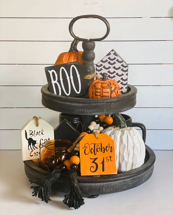 a classic Halloween stand with bright beads, orange pumpkins, candle lanterns and wooden signs with Hallowene prints