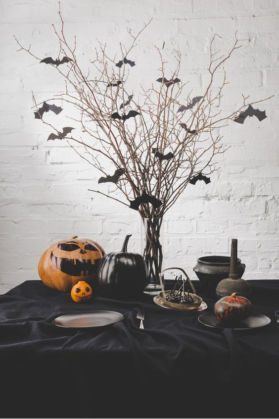 a classic Halloween table setting with bats on branches, black pumpkins and a painted orange one, a black tablecloth