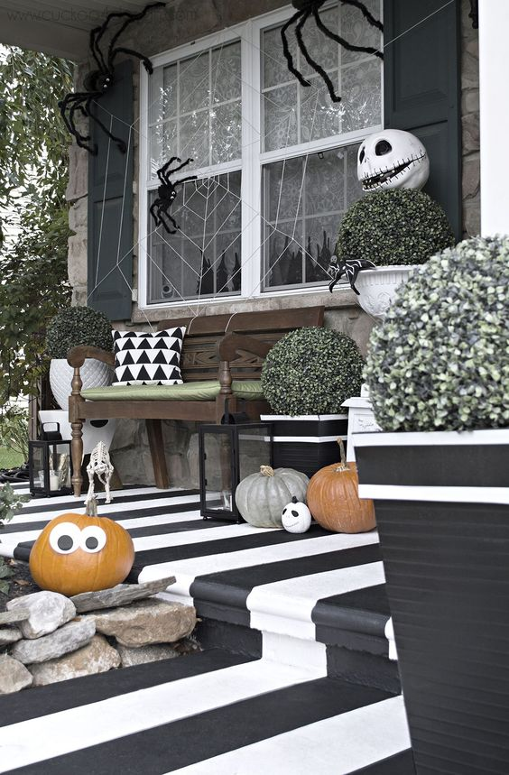 a classic black and white Halloween porch with pumpkins, scary heads, spiders and spider web
