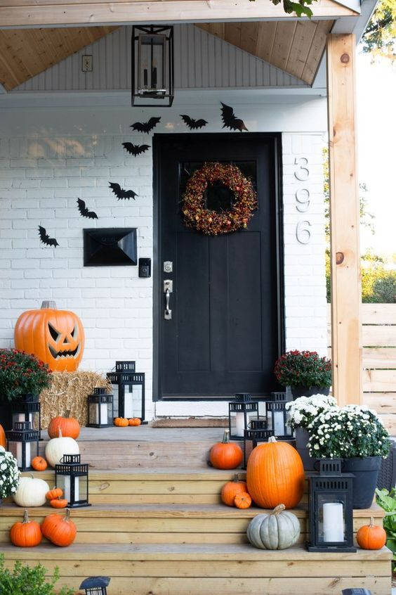 a classic front porch with bats, lots of bright pumpkins, hat, candle lanterns and a bold fall wreath