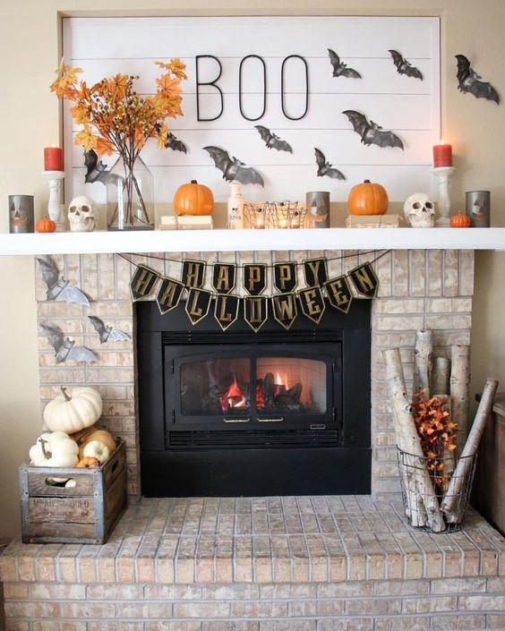 a classic rustic Halloween fireplace with grey bats, orange and grey candles, pumpkins and fall leaves