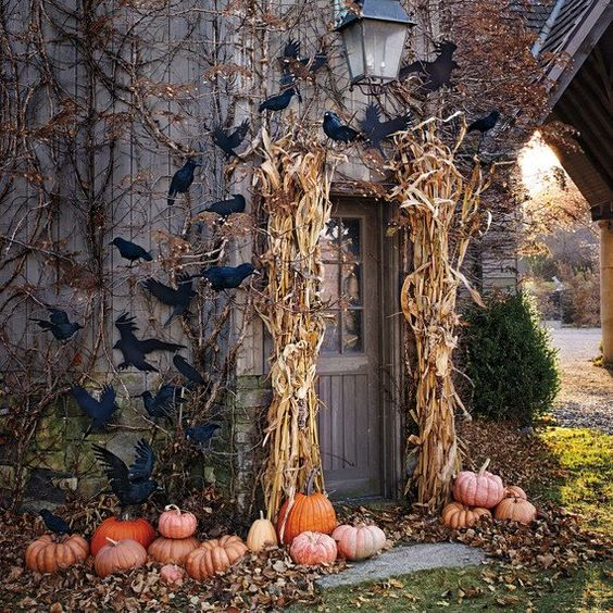 a classic rustic Halloween porch with corn husks, pumpkins, blackbirds looks scary yet not too much