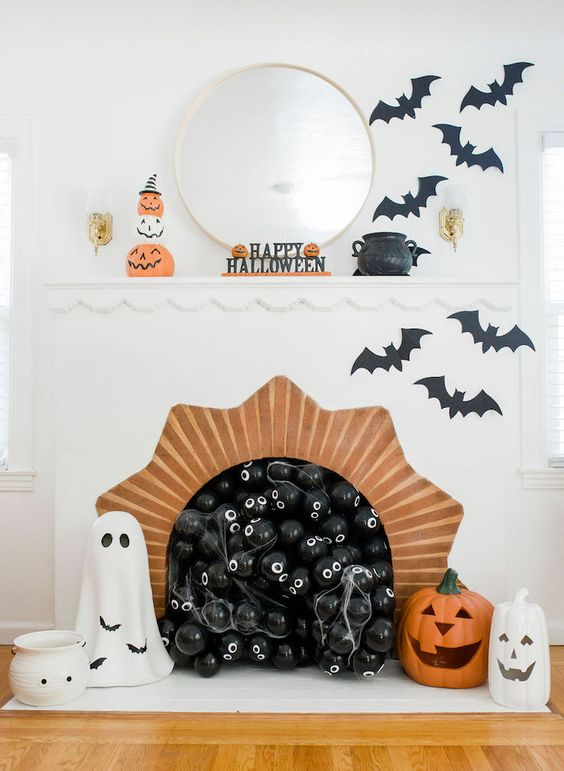 a classy Halloween fireplace with black eyed balls, black bats, ghosts and jack-o-lanterns