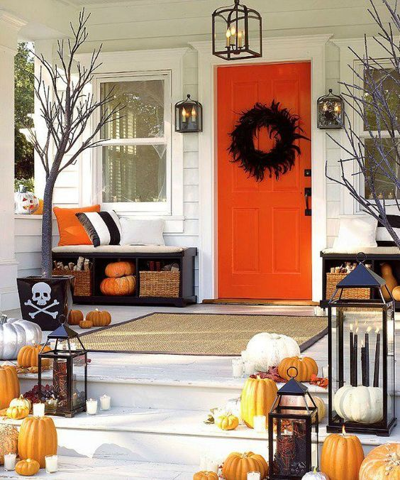 a colorful Halloween front porch with orange pumpkins, candles, a feather wreath and candle lanterns
