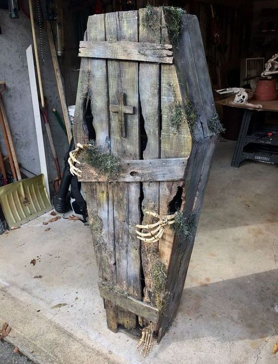 a creepy old coffin with hay and skeleton hands is a stylish rustic Halloween decoration to rock