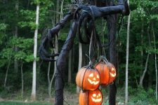 a giant Halloween reaper with a pumpkin lantern head and some adidtional lanterns in his hands is a scary statement for outdoors