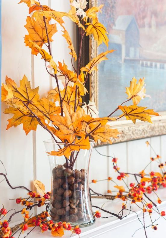a glass filled with acorns and with branches with yellow leaves and blooming branches make the mantel look very bold and fall-like
