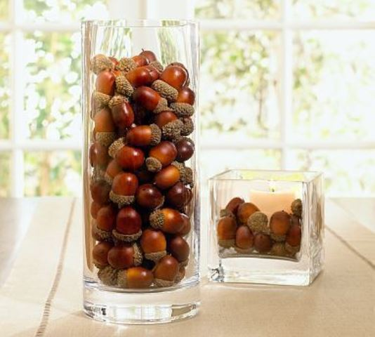 a glass with acorns and a square glass with a candle and acorns for decorating your space