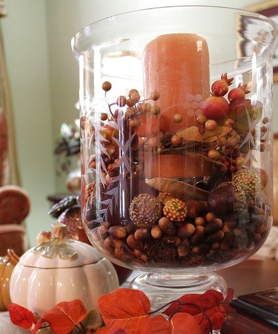 a glass with crons, faux berries, balls, seeds and an orange pillar candle for a long-lasting centerpiece