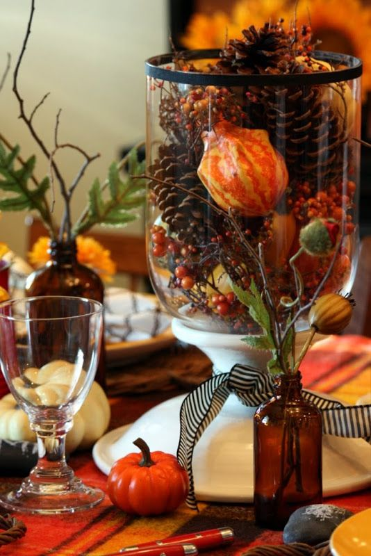 a glass with faux berries, pinecones, gourds and pumpkins is a cool and long-lasting fall centerpiece
