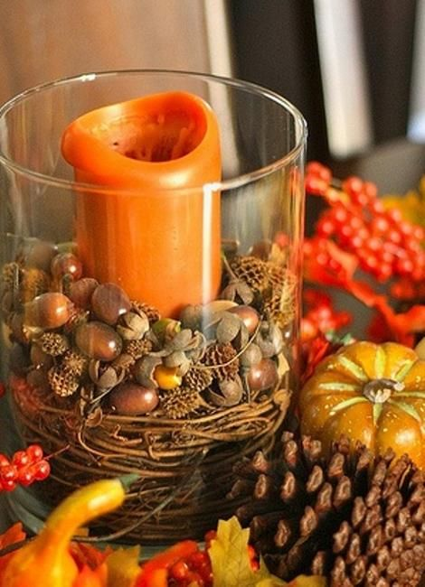 a glass with vine, acorns and nuts and an orange pillar candle is a cool and easy rustic decoration