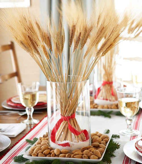 a glass with wheat and a red ribbon placed on a tray with nuts is a cool fall to winter centerpiece