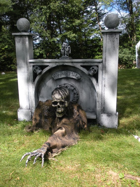 a grave with a skeleton creeping is a very scary and bold idea to decorate your front or backyard for Halloween