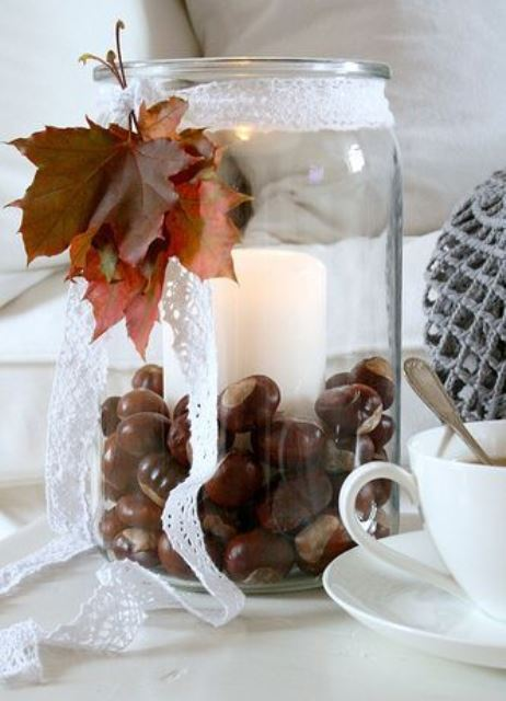 a jar with a pillar candle and nuts decorated with lace ribbon and dried leaves for fall decor