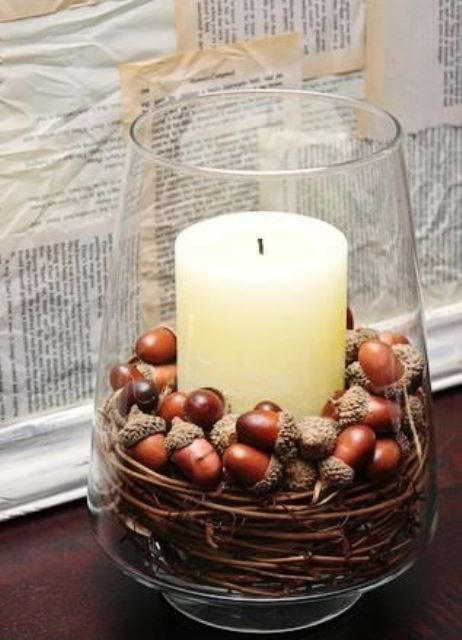 a large glass with a pillar candle, vine and acorns is a cool fall decoration that you can make very fast