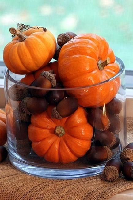 a large glass with acorns and pumpkins is a cool and very easy fall decoration that you can make last minute