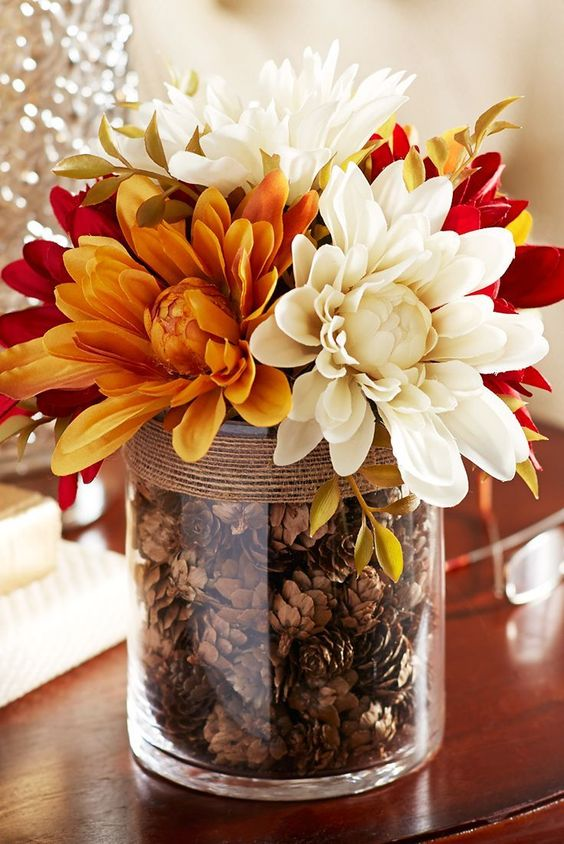 a large glass with pinecones and twine, with bright, red and white blooms is a cool fall arrangement