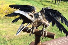 a raven skeleton prop on a rustic wooden perch is a great Halloween decor idea to try