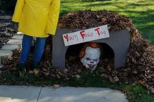 a scary Halloween decoration inspired by the It – a clown head, a sign and a yellow trench