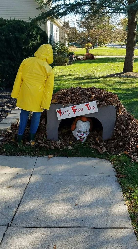 a scary Halloween decoration inspired by the It - a clown head, a sign and a yellow trench