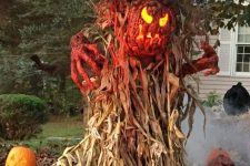 a scary outdoor decoration of corn husks, pumpkin lanterns, a bloody pumpkin and hands is fantastic