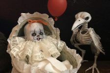 a spooky Halloween decoration of a raven skeleton and a baby in a crib with a red balloon inspired by the It