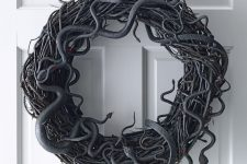 a spooky Halloween vine wreath with lots of snakes is a lovely and bold idea for wall decor