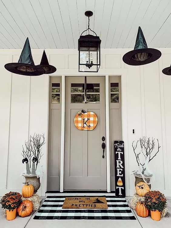 a stylish Halloween front porch with witch legs, witch hats, orange pumpkins and blooms