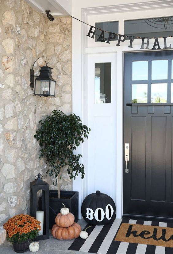 a stylish Halloween porch with stacked pumpkins and a black one, a paper bunting and some bright flowers