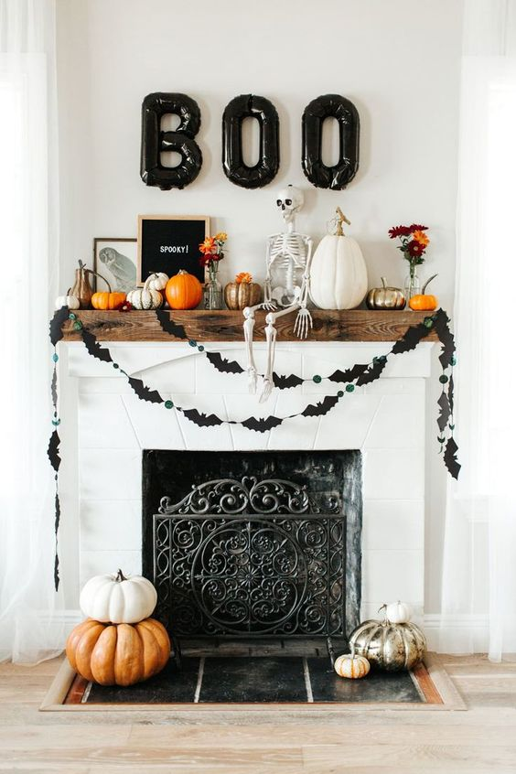 a stylish rustic Halloween mantel with black balloons, a bat bunting, lots of pumpkins, a skeleton and blooms