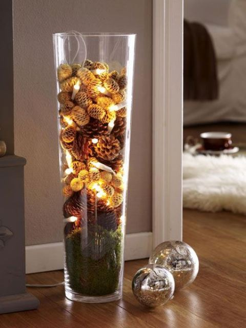 a tall glass vase filled with moss, various pinecones, dried blooms and lights is a natural fall decoration