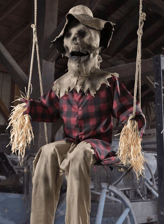 a very spooky outdoor Halloween decoration - a scarecrow dressed as a man is a cool and stylish idea