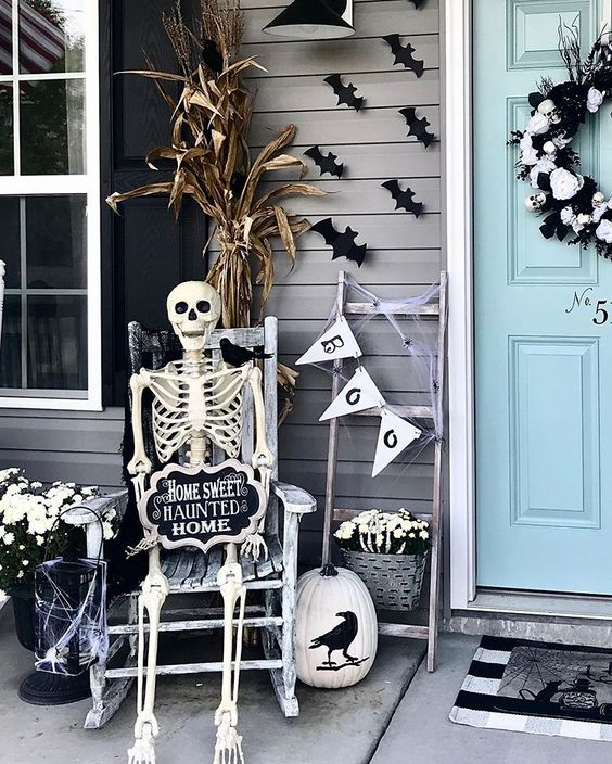 an elegant black and white Halloween porch with a skull wreath, a skeleton, a web candle lantern and some white blooms