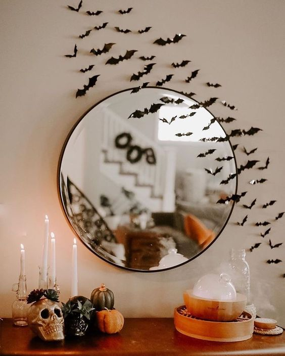 chic Halloween decor with bats, pumpkins, candles, a skull and some fog is a mistical decor idea