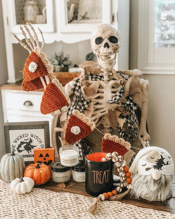 classic Halloween decor with a skeleton, a crocheted pumpkin pie garland, pumpkins, candles and beads is lovely