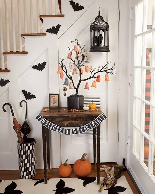 classic Halloween decor with bats, pumpkins and a Halloween tree with favors hanging on it