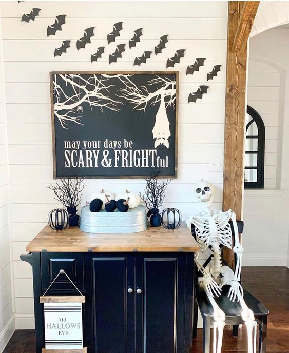 classic black and white Halloween decor with bats, black and white pumpkins, a skeleton and a cool sign