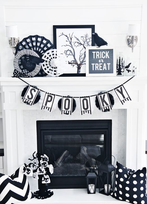 classic black and white Halloween fireplace decor with paper doilies, fake birds, candle lanterns, a bunting and a mini tree