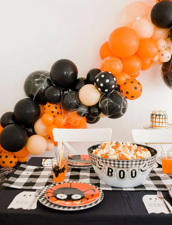 classic bright Halloween styling with fun plates, candy corn in a bowl and a large orange and black balloon garland