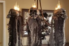 elegant and scary Halloween decor – a chandelier with skulls and black fabric down is a fantastic idea